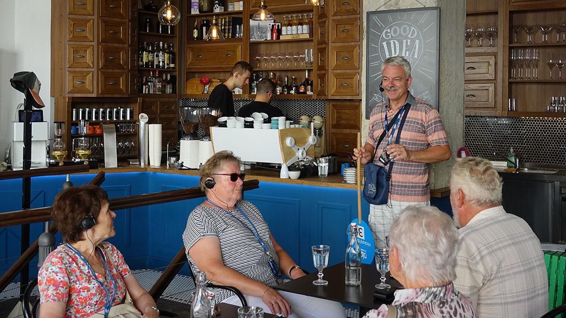 Reiseleiter gibt in einem Café Erklärungen zur Stadt ab